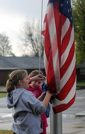 """Macie McCollum (left) and Courtney Petersen take care of """"Old Glory"""" and the Oklahoma flag after heavy rains began to fall at Chisholm Elementary School Wednesday, May 1, 2013. The fourth grade students noticed the rain and knew that they needed to bring the flags inside. (Staff Photo by BONNIE VCULEK)"""