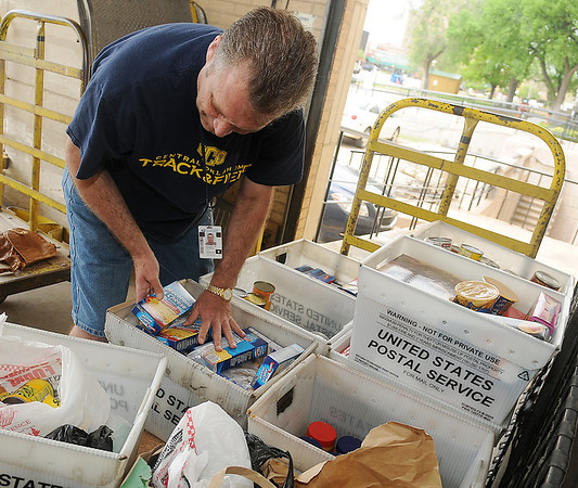 Postmaster Jeffrey Carroll packs collected food items into United States Postal Service containers as mail carriers arrive at the Enid Post Office with non-perishable items during the Stamp Out Hunger Food Drive Saturday, May 11, 2013. More than 13,000 pounds of food will be donated to the Horn of Plenty during the annual event. (Staff Photo by BONNIE VCULEK)
