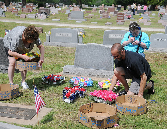 Marsha Harmon (left), from Moore, Troy Harmon and their nephew Lance Richardson, from Oklahoma City, decorate their family graves at Enid Cemetery Saturday, May 25, 2013. Even though Marsha Harmon's home was destroyed in the Moore tornado Monday, she paused to remember her loved one Memorial Day weekend. (Staff Photo by BONNIE VCULEK)