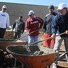Craig Box (center) and Clint Chelf (right) mix concrete in the new Champion Park Saturday, May 4, 2013. The workday at 10th and Chestnut, the former location of Wilson Elementary School, was sponsored by the Austin Box Foundation. Austin Box, who was a star athlete at Enid High School and the University of Oklahoma football team, died May 19, 2011, of an overdose of painkillers. The new park designed by Whitney Box, director of strategic and long-range planning for Enid, will be an athletic park to get kids moving and more active. (Staff Photo by BONNIE VCULEK)