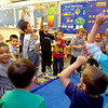 Enid Public Schools' Pre-K students leap into the air as they sing during activity time in Joan Dodd's classroom Thursday, May 15, 2014. (Staff Photo by BONNIE VCULEK)