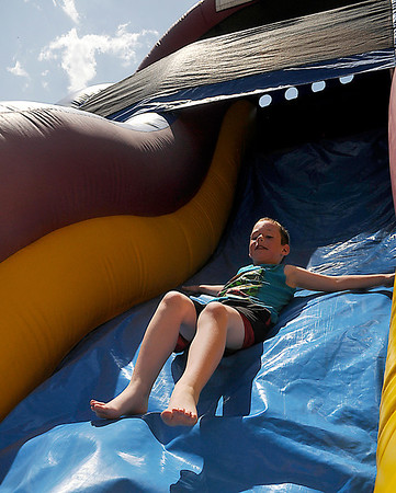 Logan Alley slides an inflatable during the Hoover Elementary School block party Saturday. (Staff Photo by BILLY HEFTON)