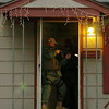 A law enforcement officer stands in the doorway of an Enid residence where two men were arrested during a large-scale drug sweep Thursday, May 8, 2014. (Staff Photo by BONNIE VCULEK)