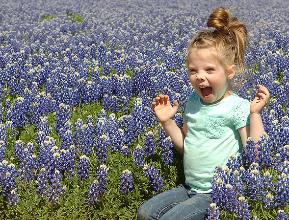 Reagan Lenamond, daughter of Micah and Amanda Lenamond from Enid, laughs as she plays in a field of Blue Bonnets on Oakwood Road Saturday, May 3, 2014. (Staff Photo by BONNIE VCULEK)