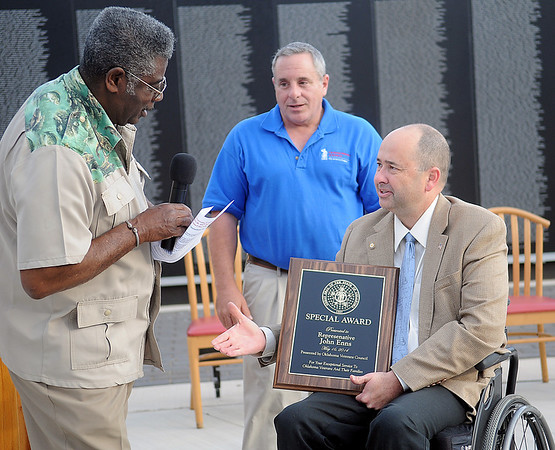 Rep. John Enns (right) receives a special award from the Oklahoma Veterans Council for exceptional service to Oklahoma veterans and their families during a Vietnam Memorial Wall Name Placement Ceremony at Enid Woodring Regional Airport Friday, May 16, 2014. (Staff Photo by BONNIE VCULEK)