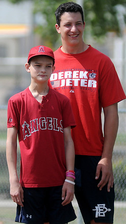 Conner Ganz (left) and his brother, Corey, await the next Angels' hit as they run the bases together during Miracle League games at AMBUCS ABC Park Saturday, May 31, 2014. Each Saturday in May and June, children and adults with special needs, play on the new Miracle League artificial turf. (Staff Photo by BONNIE VCULEK)