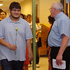 Noel Fuerte (left) processes past Jarry Hillman, Lincoln Academy principal, as Fuerte enters the Emerson Middle School auditorium for Senior Appreciation Night Thursday, May 15, 2014. Fuerte was among 85 Lincoln Survivors honored during the 2014 program. (Staff Photo by BONNIE VCULEK)