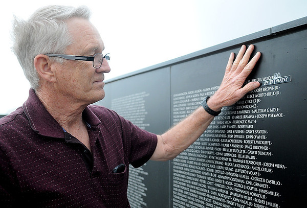 Ken Parker posts the name of his brother, Lester J. Veazey, on the Vietnam Memorial Wall during a special ceremony at Enid Woodring Regional Airport Friday, May 16, 2014. (Staff Photo by BONNIE VCULEK)