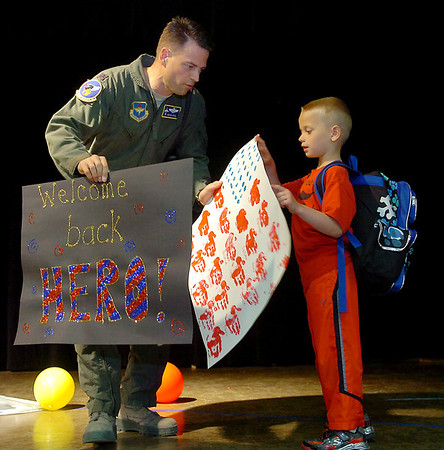 Lt. Col. Kevin Kohl and his son, Austin, carry signs made  by Chisholm Elementary School upon Kohl's return from Iraq Friday, May 2, 2014. Lt. Col. Kohl surprised his children, Grace and Austin, during Wilson the Clown's magic show. (Staff Photo by BONNIE VCULEK)