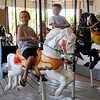 Caden Bitakis and Ethan Moody (from left) ride the Carousel at Meadowlake Park after the grand opening and ribbon cutting ceremony Thursday, May 22, 2014. Bill Moody, the boys' father, was one of the City of Enid employees that helped restore the carousel. (Staff Photo by BONNIE VCULEK)