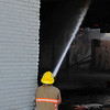 An Enid firefighter spray water onto the ceiling while fighting a structure fire at Grand and Park Sunday. (Staff Photo by BILLY HEFTON)