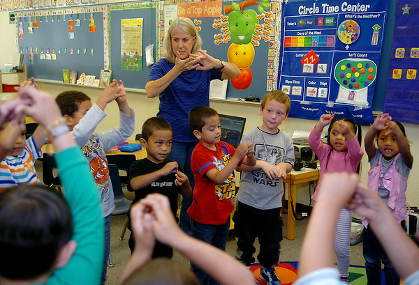 """Joan Dodds, the pre-K teacher at Northern Oklahoma College, sings """"Ittsy Bitsy Spider"""" with her students Thursday, May 15, 2014. After morning activities in the classroom, Dodds walks her students across Randolph to the Adams Elementary School cafeteria for lunch before returning for outside games. (Staff Photo by BONNIE VCULEK)"""