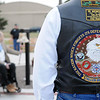 "Memorial insignias appear on a United States Veteran's vest (right) as Rep. John Enns rings a bell during the national ""Carry the Flame Across America"" torch ceremony at the Vietnam Memorial Wall, Enid Woodring Regional Airport Friday, May 16, 2014. (Staff Photo by BONNIE VCULEK)"
