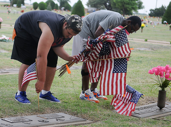 Hunter Chapman and Xavier Prince honor veterans as they place United States flags on their graves at Memorial Park Cemetery Friday, May 23, 2014. Enid High School Plainsmen football and baseball players spent several hours at Memorial Park Cemetery and Enid Cemetery during the Memorial Day weekend event. (Staff Photo by BONNIE VCULEK)