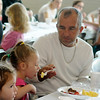 A father helps his daughter eat at the Denny Price Family YMCA Father/Daughter breakfast Saturday, May 17, 2014. (Staff Photo by BONNIE VCULEK)