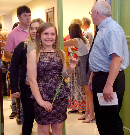 Rylee Moritz and Kaylee Morrison (left) process past Jarry Hillman, Lincoln Academy principal, as 85 Lincoln Academy Survivors enter the Emerson Middle School auditorium for Senior Appreciation Night Thursday, May 15, 2014. (Staff Photo by BONNIE VCULEK)