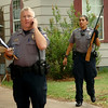 Lt. Eric Holtzclaw (left) directs law enforcement officials at an Enid location as another Enid Police Officer removes a gun from an Enid home after two men were arrested during a large-scale drug sweep Thursday, May 8, 2014. (Staff Photo by BONNIE VCULEK)