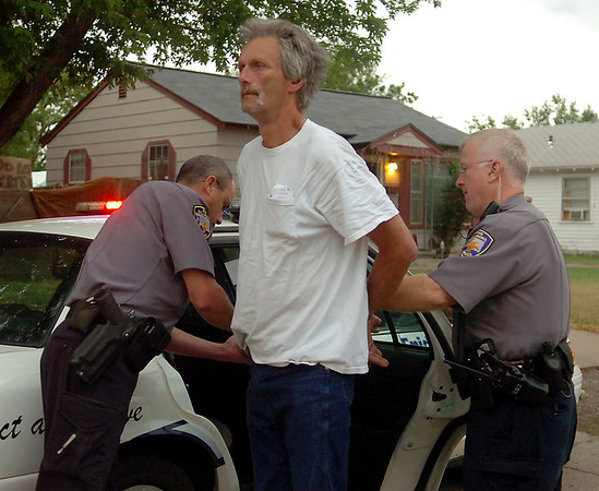 Enid Police Officers arrest Jack Rowland during a large-scale drug sweep Thursday, May 8, 2014. Oklahoma Bureau of Narcotics, Oklahoma Highway Patrol; Oklahoma Police; Enid Police Department and the Garfield County Sheriff Department assisted with the early morning sweep. (Staff Photo by BONNIE VCULEK)