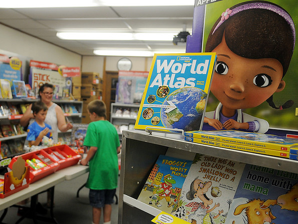 Individuals select books during the Public Library of Enid and Garfield County Scholastic book fair Wednesday, May 28, 2014. The event runs through Friday, and all proceeds help purchase new reading materials for the library. (Staff Photo by BONNIE VCULEK)