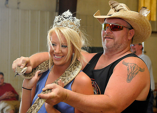 Todd Felder holds the winning snake at the 75th Annual Okeene Rattlesnake Round-up around the neck of the Whea-esta Queen, Olivia Westfahl, Sunday in Okeene. The winning snake measured 77 inches. (Staff Photo by BILLY HEFTON)
