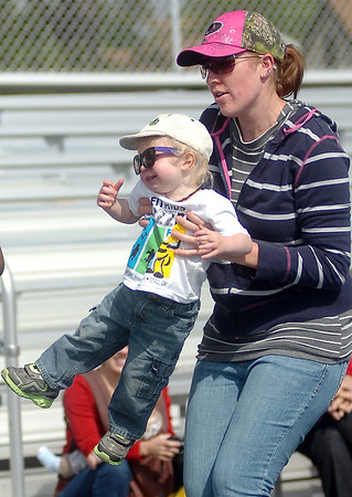 A mother carries her toddler across the finish line during the 5th annual Be Fit Kids Buzz Run Saturday, May 17, 2014. (Staff Photo by BONNIE VCULEK)