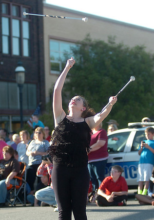 An Enid Twirling Academy performer tosses a baton into the air as the group pauses in front of the judge's stand during the 82nd annual Tri-State Parade Friday, May 2, 2014. (Staff Photo by BONNIE VCULEK)