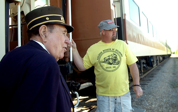Watermelon Campbell (left), a conductor for the Frisco Line for many years, and his son, Stephen Case, wait for the last individuals to arrive for the Farmrail Train ride from Enid to Okeene Saturday, May 3, 2014. The train departed Enid shortly after 9 a.m. for the trip to the 75th annual Okeene Rattlesnake Hunt. (Staff Photo by BONNIE VCULEK)