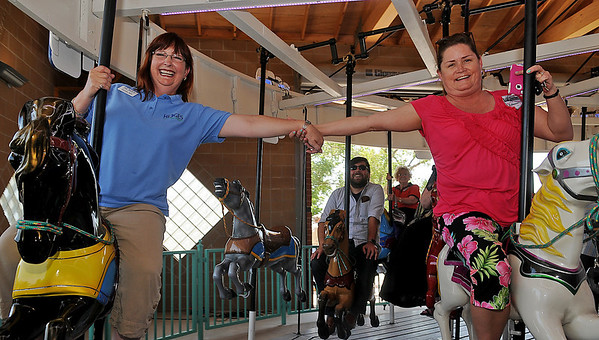 Carmen Ball (left), Ben Ezzell (back center) and Tricia Mitchell ride the restored Kiwanis Carousel following the ribbon cutting ceremony at Meadowlake Park Thursday, May 22, 2014. (Staff Photo by BONNIE VCULEK)