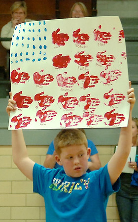Cason Blosser, from Chisholm Elementary School, holds up a patriotic sign for Lt. Col. Kevin Kohl, who just returned from a six-month deployment to Iraq. Kohl surprised his children, Grace and Austin, during a magic trick at their school Friday, May 2, 2014. (Staff Photo by BONNIE VCULEK)