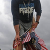 Steve Chard, head football coach for the Enid High School Plainsmen, places a United States flag on the grave of a veteran at Memorial Park Cemetery Friday, May 23, 2014. (Staff Photo by BONNIE VCULEK)