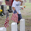 Caelin Ellis honors United States Veterans Memorial Day weekend as he places flags on the Enid Cemetery graves Friday, May 23, 2014. (Staff Photo by BONNIE VCULEK)