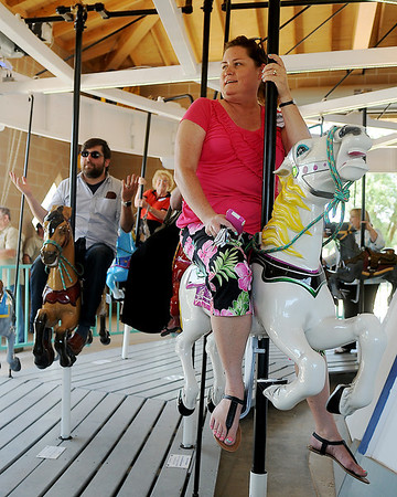 Ben Ezzell, Tricia Mitchell and other dignitaries ride the Carousel at Meadowlake Park after the grand opening and ribbon cutting Thursday, May 22, 2014. (Staff Photo by BONNIE VCULEK)
