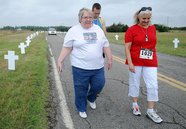 Jill Hake (left) and Debra Lafon walk past the Woodring Wall of Honor crosses that honor their sons and more than 100 others who lost their lives serving their country during the Red Dirt Run of Honor Saturday, May 24, 2014. (Staff Photo by BONNIE VCULEK)