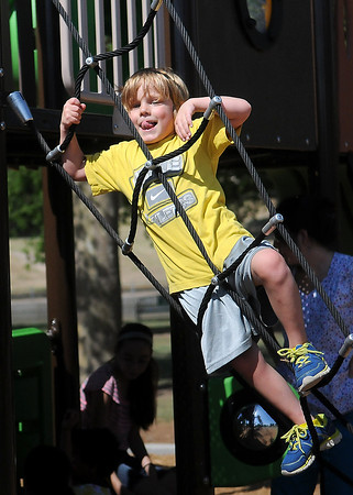 Noah Eisele climbs a rope ladder at Government Springs Park as he plays with other McKinley Elementary School kindergarten students during the last day of school Thursday, May 22, 2014. (Staff Photo by BONNIE VCULEK)