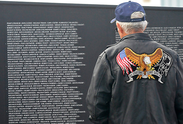 A Vietnam veteran stares at the Vietnam Memorial Wall prior to the Woodring Wall of Honor Memorial Day ceremonies Monday. (Staff Photo by BILLY HEFTON)