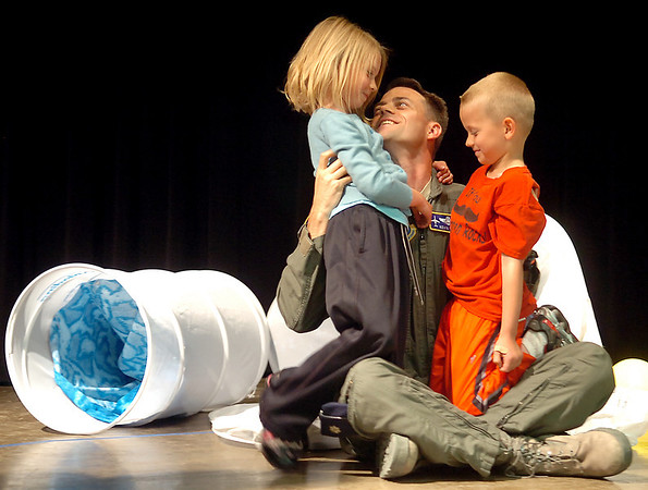 Lt. Col. Kevin Kohl (center) surprises his children, Grace and Austin, when he appeared from under a giant science beaker during Wilson the Clown's magic show at Chisholm Elementary School Friday, May 2, 2014. Lt. Col. Kohl, who has been stationed in Iraq for six months, and his wife Melissa, planned the event with the help of Sara Dow and Dan Luskey. (Staff Photo by BONNIE VCULEK)