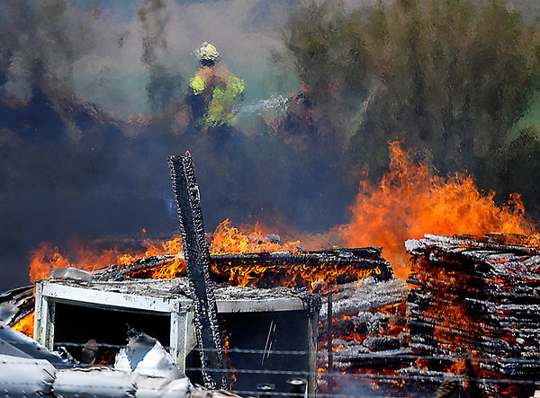 Enid firefighters work the edges of a pallet fire on east Chestnut to keep it from spreading Monday. (Staff Photo by BILLY HEFTON)
