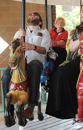 Ben Ezzell, Mary Feightner and Tammy Wilson (from left) ride the Carousel following the grand opening and ribbon cutting ceremony at Meadowlake Park Thursday, May 22, 2014. (Staff Photo by BONNIE VCULEK)