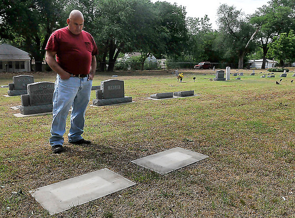 David Black looks down as he talks about finding the headstones of his mother and grandmother missing when he came to visit on Mother's Day. (Staff Photo by BILLY HEFTON)
