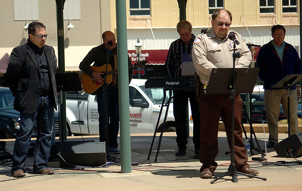Garfield County Sheriff Jerry Niles (front right) prays for the safety of  all police officers, firefighters and their loved ones during the National Day of Prayer on the Garfield County Courthouse lawn in downtown Enid Thursday, May 1, 2014. (Staff Photo by BONNIE VCULEK)