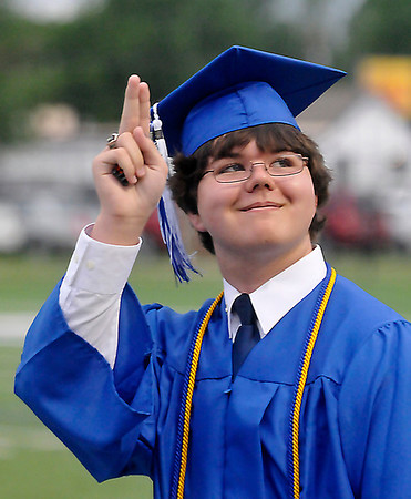 An EHS senior acknowledges the crowd as he marches in during the Enid High School Commencement Thursday at D. Bruce Selby Stadium. (Staff Photo by BILLY HEFTON)