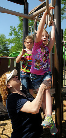 Emma Reneau concentrates as P.J. Hanscom helps her cross an obstacle on the Government Springs Park playground during the McKinley Elementary School kindergarten class fun day Thursday, May 22, 2014. (Staff Photo by BONNIE VCULEK)