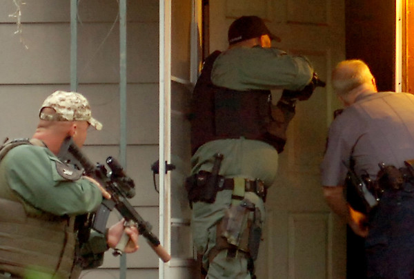 Law enforcement officers prepare to enter an Enid residence during a large-scale drug sweep Thursday, May 8, 2014. (Staff Photo by BONNIE VCULEK)