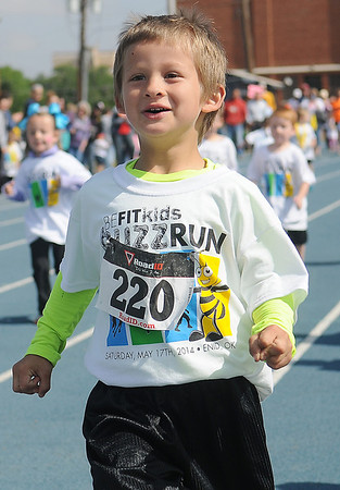 A young runner cruises to the finish line during the 5th annual Be Fit Kids Buzz Run at Enid High School Saturday, May 17, 2014. (Staff Photo by BONNIE VCULEK)