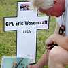 Tom Wosencraft kneels next to his son's memorial cross during the Red Dirt Run of Honor at Enid Woodring Regional Airport Saturday, May 24, 2014. CPL Eric Wosencraft was killed in the line of duty. (Staff Photo by BONNIE VCULEK)