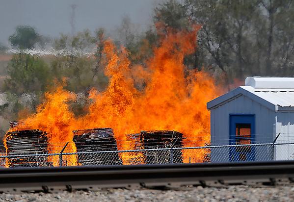 Stacks of pallets burn alon east Chestnut Monday. (Staff Photo by BILLY HEFTON)