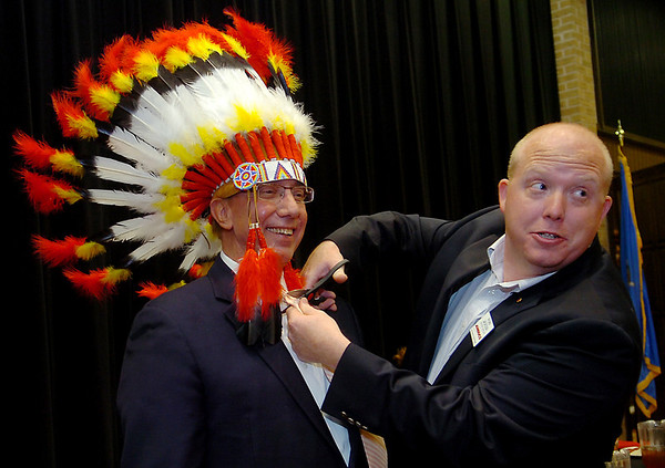 Jack Bellware (left), the AMBUCS National President, dons a traditional Indian head dress as Enid Noon AMBUCS President Ryan Jackson cuts off his tie during the noon luncheon in the NOC Enid Gantz Center ballroom Friday, May 2, 2014. The colorful head dress is presented to each national president when they visit with the Enid AMBUCS organizations. (Staff Photo by BONNIE VCULEK)