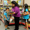 Jude, Veronica and Jamie Marin (from left) select books during the Public Library of Enid and Garfield County Scholastic book fair Wednesday, May 28, 2014. The event runs through Friday, and all proceeds help purchase new reading materials for the library. (Staff Photo by BONNIE VCULEK)