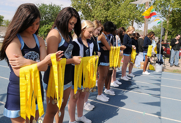 Enid High School cheerleaders pause in prayer before they hand out medals to Be Fit Kids Buzz Run sprinters Saturday, May 17, 2014. Children enjoyed inflatable games, face painting and drinks after their races at the EHS Track. (Staff Photo by BONNIE VCULEK)