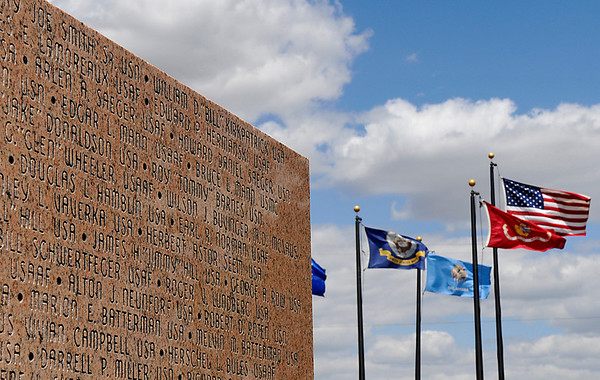 Flags wave in the steady wind Thursday at the Woodring Wall of Honor. (Staff Photo by BILLY HEFTON)